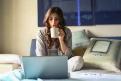 woman-in-grey-jacket-sits-on-bed-uses-grey-laptop-935743 (1)